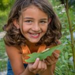 Young girl looking at Monarch caterpillar. Photo by Brett Billings/USFWS